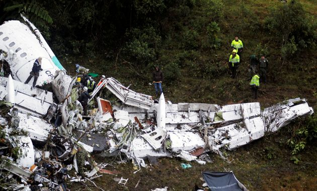 Rescue crew work in the wreckage from a plane that crashed into Colombian jungle with Brazilian soccer...