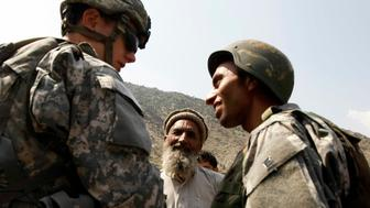 Lieutenant Cumbie (L) of the U.S. Army's Dagger Company, 2-12 Infantry, 4th Brigade and an Afghan interpreter (R) talk to a village elder in Kolack in the Pesh Valley in Afghanistan's Kunar Province July 21, 2009.     REUTERS/Tim Wimborne    (AFGHANISTAN POLITICS MILITARY)