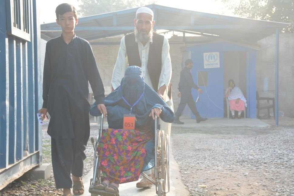Roz Qul, 55, and his family walk through the UNHCR repatriation camp in Peshawar, Pakistan. Qul and his family are headed bac