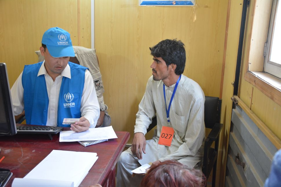 A UNHCR official checks the identification card of Musa Khan, 32, as he goes through the process of repatriation to Afghanist