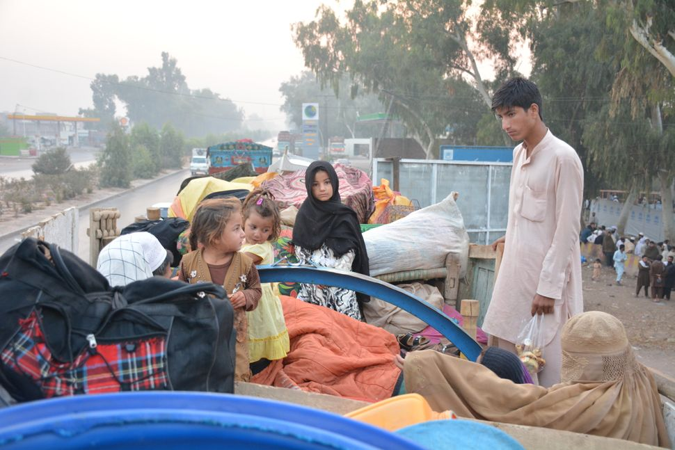 The family of Abdul Rahim sits with all of their belongings at the repatriation center in Peshawar, Pakistan. His family