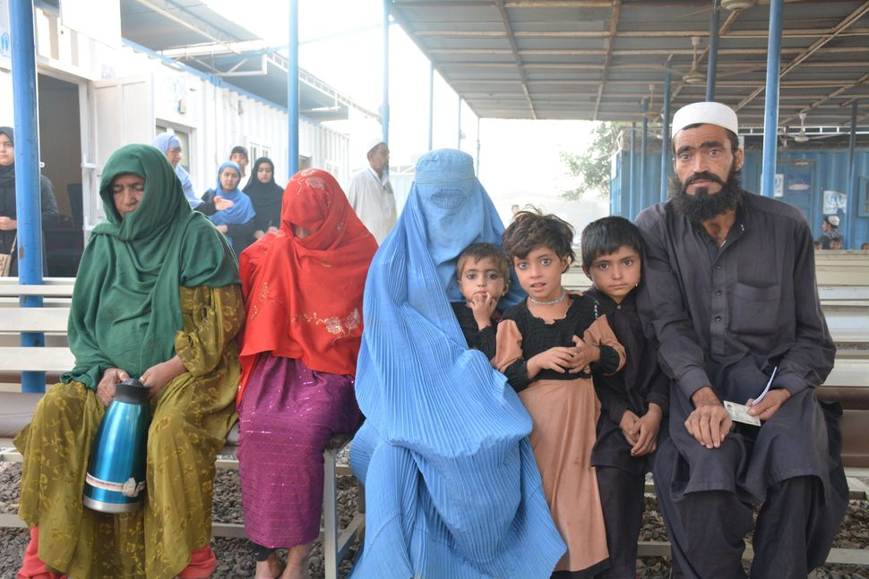 A family sits on a bench at the UNHCR repatriation center in Peshawar, Pakistan while they wait for their forms to be approve