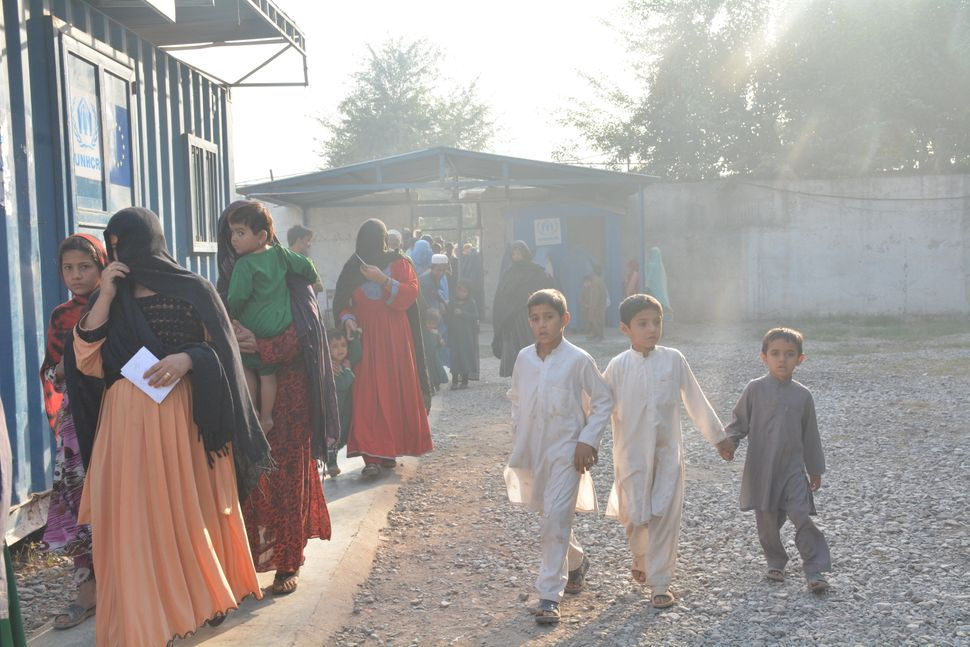 Children run around a UNHCR repatriation center in Peshawar as families wait in line to have their paperwork approved to