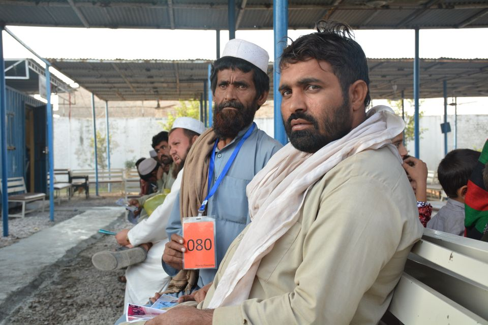 Two men sit and wait for their number to be called to complete the repatriation process. Each refugee family is allotted an i