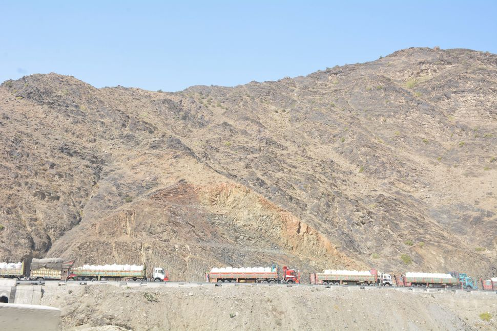 Large trucks carry the belongings of Afghan refugees as they make their way towards the Torkham border to resettle in their n