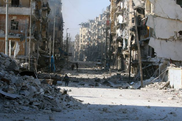 Syrians walk over rubble of damaged buildings in Aleppo. Experts warned there were direct links to climate...