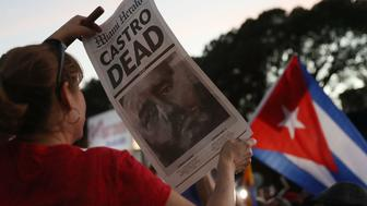 MIAMI, FL - NOVEMBER 26:  A person holds a poster printed by the Miami Herald with a headline that reads  that the former Cuban President Fidel Castro is dead as they react to the news of his death outside the restaurant Versailles on November 26, 2016 in Miami, Florida. Many, mostly Cubans, gathered to wave flags and celebrate the news of the death of the Cuban revolutionary who died at 90.  (Photo by Joe Raedle/Getty Images)
