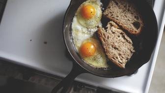 Eggs over-easy and bread frying in a cast iron pan for breakfast.