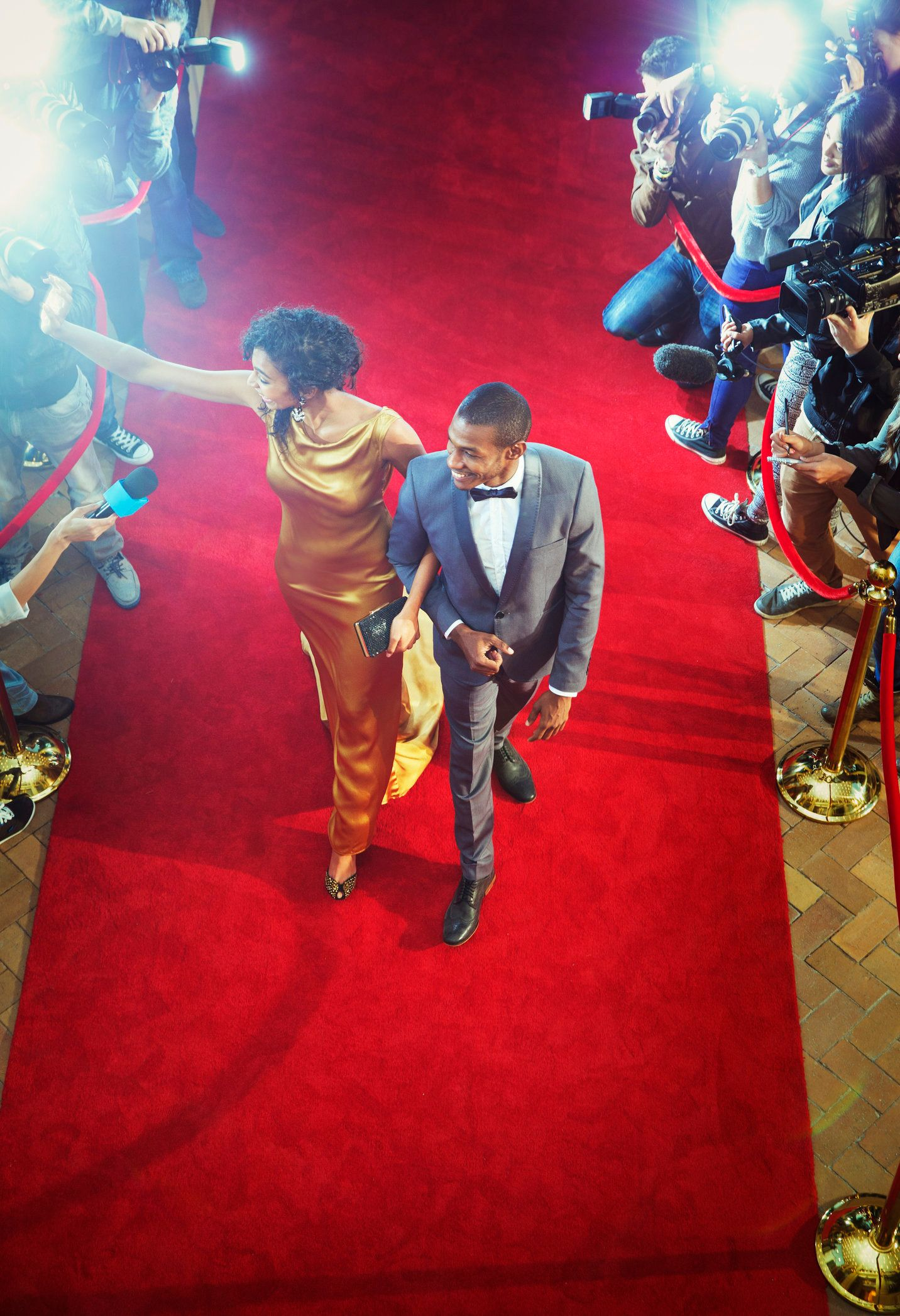Celebrity couple arriving at event waving and walking the red carpet