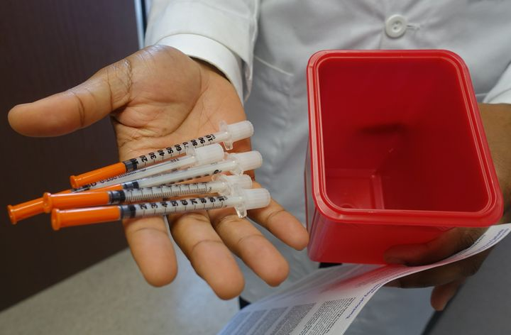 Hansel Tookes, a doctor at the University of Miami, holds needles on November 30, 2016, that will be given away to addicts at