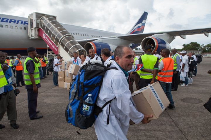 The first members of a team of 165 Cuban doctors and health workers unload medical supplies at the airport in Freetown, Sierra Leone, as they arrive to help fight Ebola in 2014.