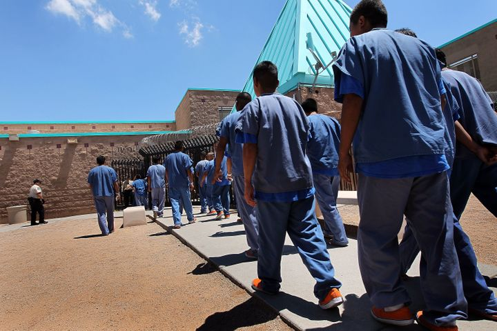 Detained immigrants walk back to their housing units following lunch at the U.S. Immigration and Customs Enforcement (ICE) de