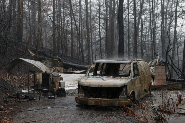 The remains of a van and home smolder in the wake of a wildfire Wednesdayin Gatlinburg, Tennessee.