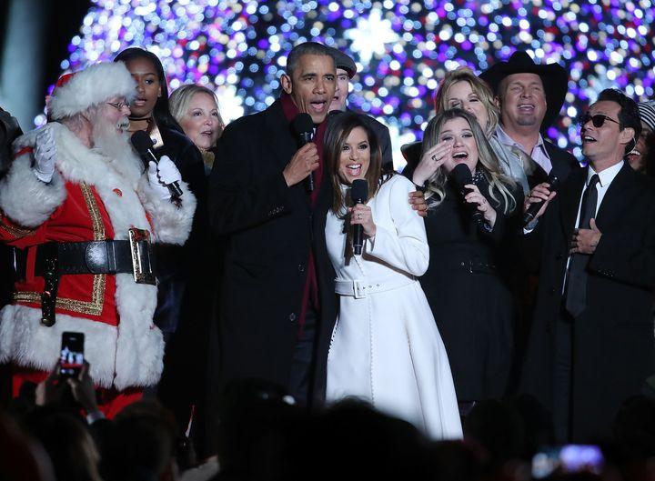 """President Barack Obama sings """"Jingle Bells"""" with, from left, daughter Sasha, Caroline Smedvig, James Taylor, Eva Longoria, Ke"""