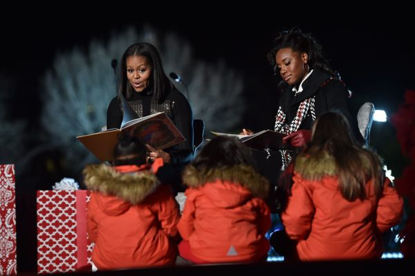 First lady Michelle Obama reads to children at the National Christmas Tree Lighting with Simone Manuel, thefirst female