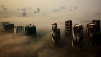 Buildings in construction are seen among mist during a hazy day in Rizhao, Shandong province, China, October 18, 2015. REUTERS/Stringer CHINA OUT. NO COMMERCIAL OR EDITORIAL SALES IN CHINA      TPX IMAGES OF THE DAY