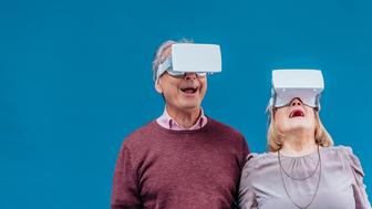 Portrait of an impressed and amazed elderly man and woman mouth and hands open wearing a 3D virtual reality (VR) headset in virtual reality experience. Blue background and copy space areas