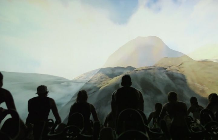 Cyclers during an IMAX Shift watch moving images of mountains.