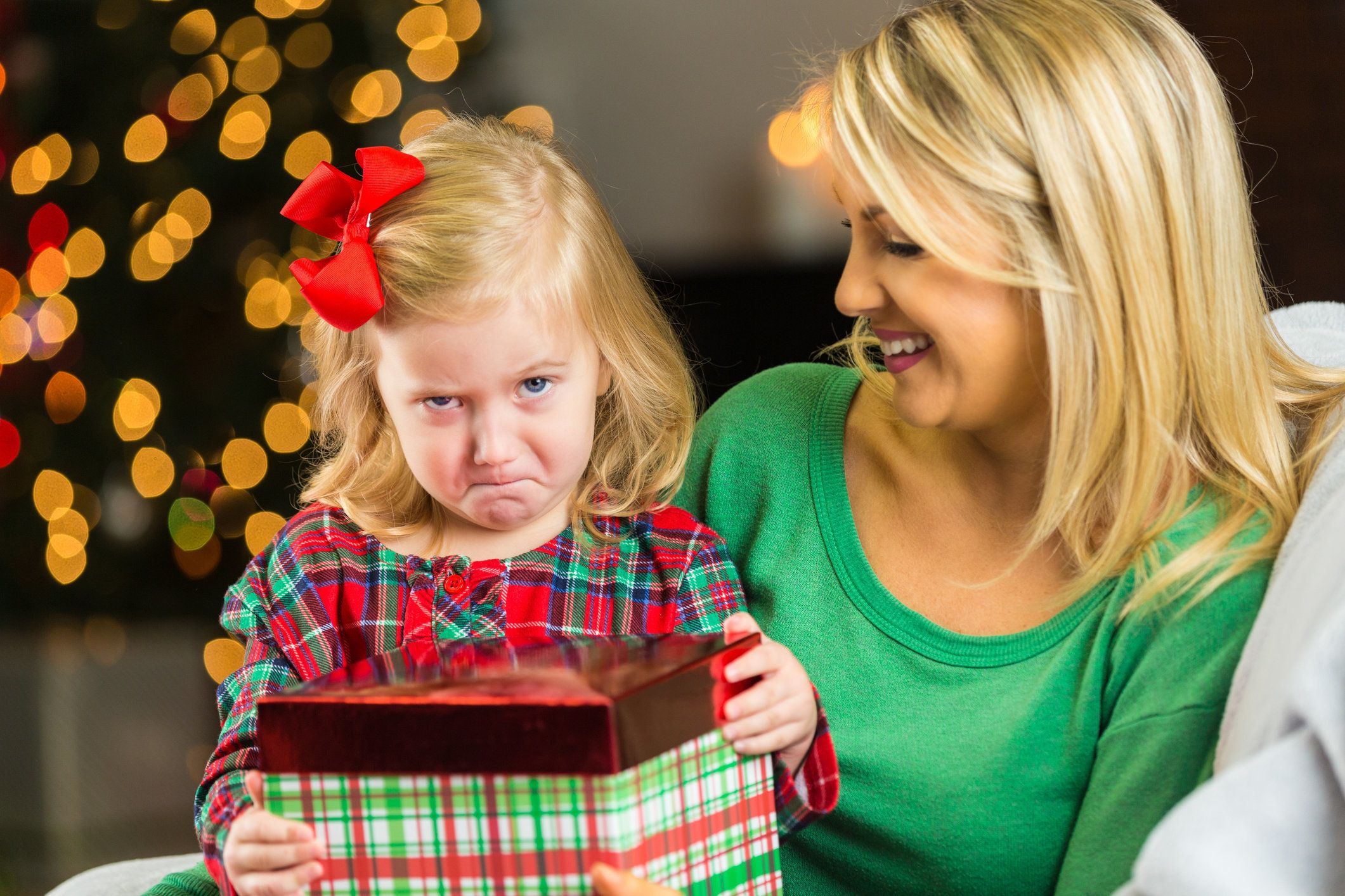 Disappointed little girl holding Christmas present while frowning with mom