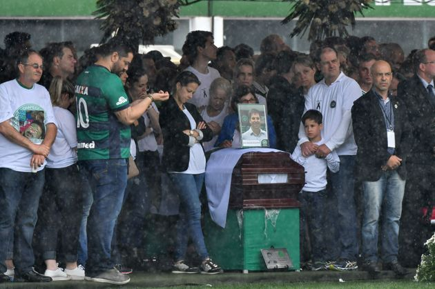 Relatives mourn over the coffin of Chapecoense football club staff member Sebastiao Burtet