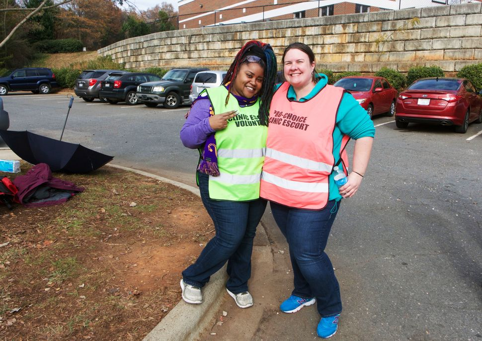 Two volunteer clinic escorts wait for patients outside the clinic.
