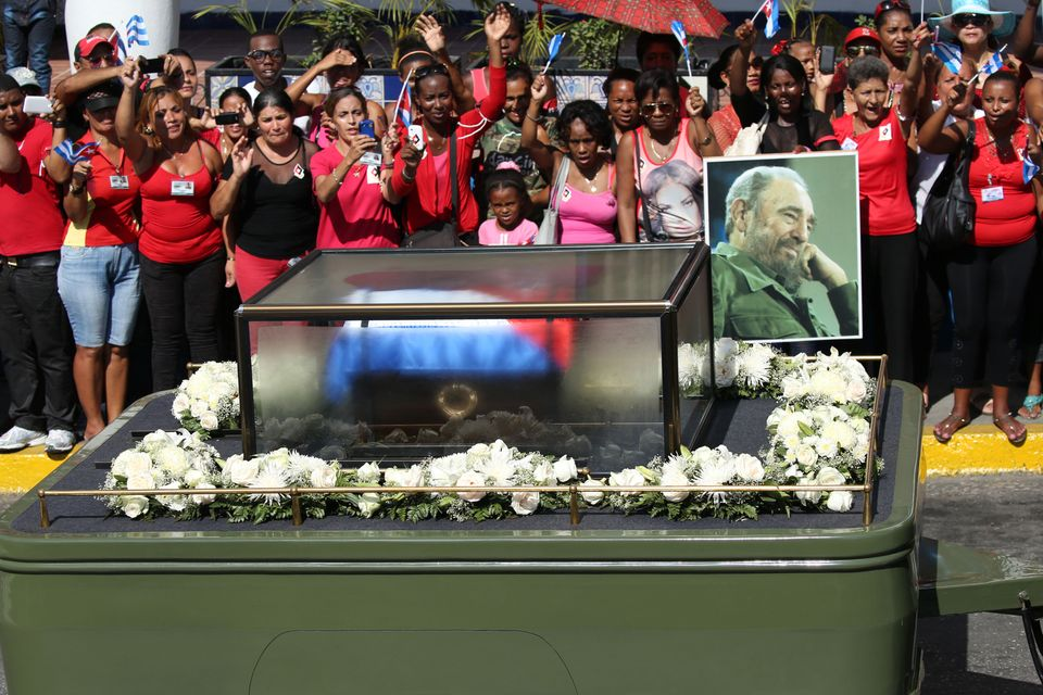 Residents wave as the caravan carrying the ashes of Cuba's late President Fidel Castro arrives in Santiago...