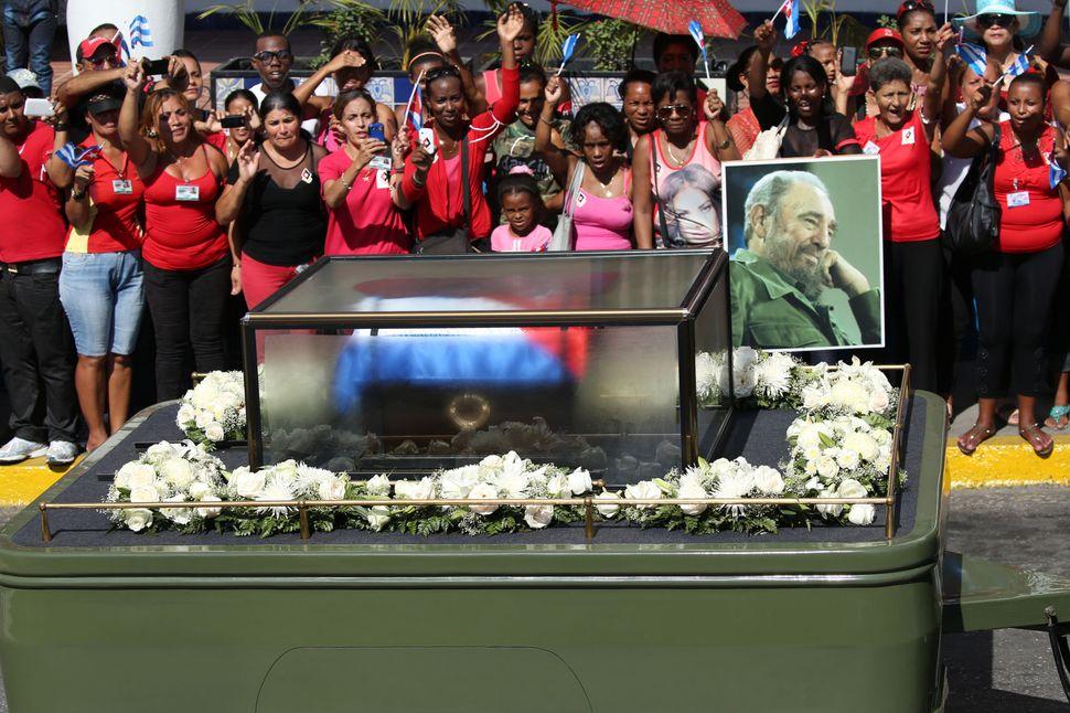 Residents wave as the caravan carrying the ashes of Cuba's late President Fidel Castro arrives in Santiago de Cuba, Cuba, Dec