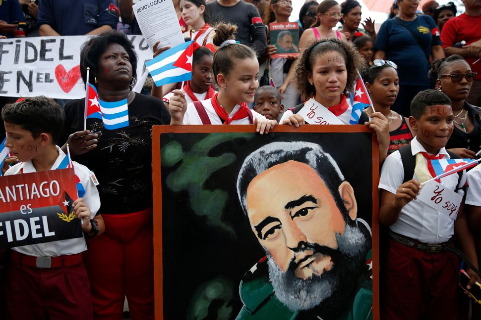 Schoolchildren wave Cuban flags while holding a portrait of Cuba's late President Fidel Castro as the caravan carrying Castro
