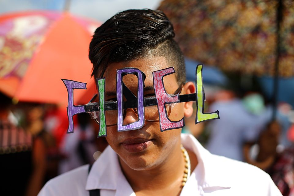A student wears decorated eyeglasses as the caravan carrying the ashes of Cuba's late President Fidel...
