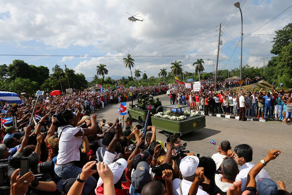 People line a street to watch as the caravan carrying the ashes of Cuba's late President Fidel Castro...