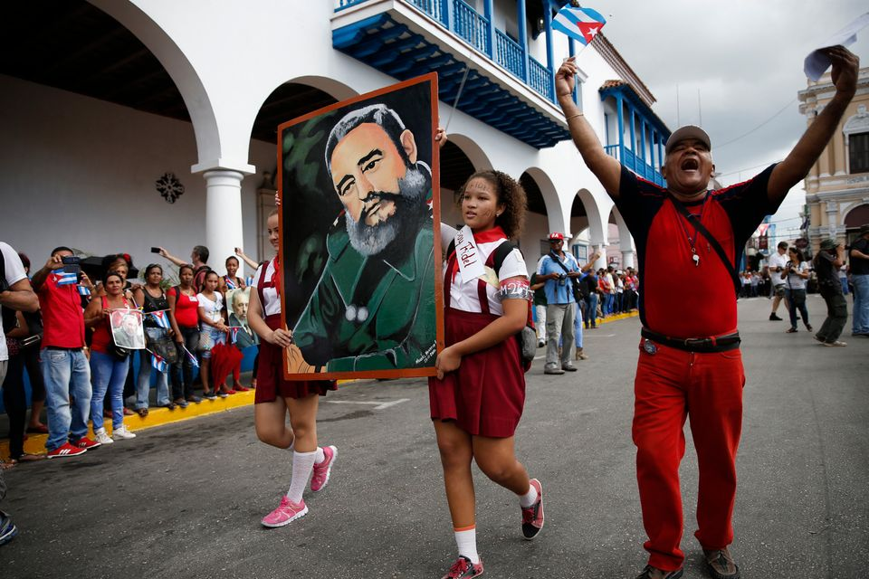 Students carry a portrait of Cuba's late President Fidel Castro as the caravan carrying Castro's ashes...
