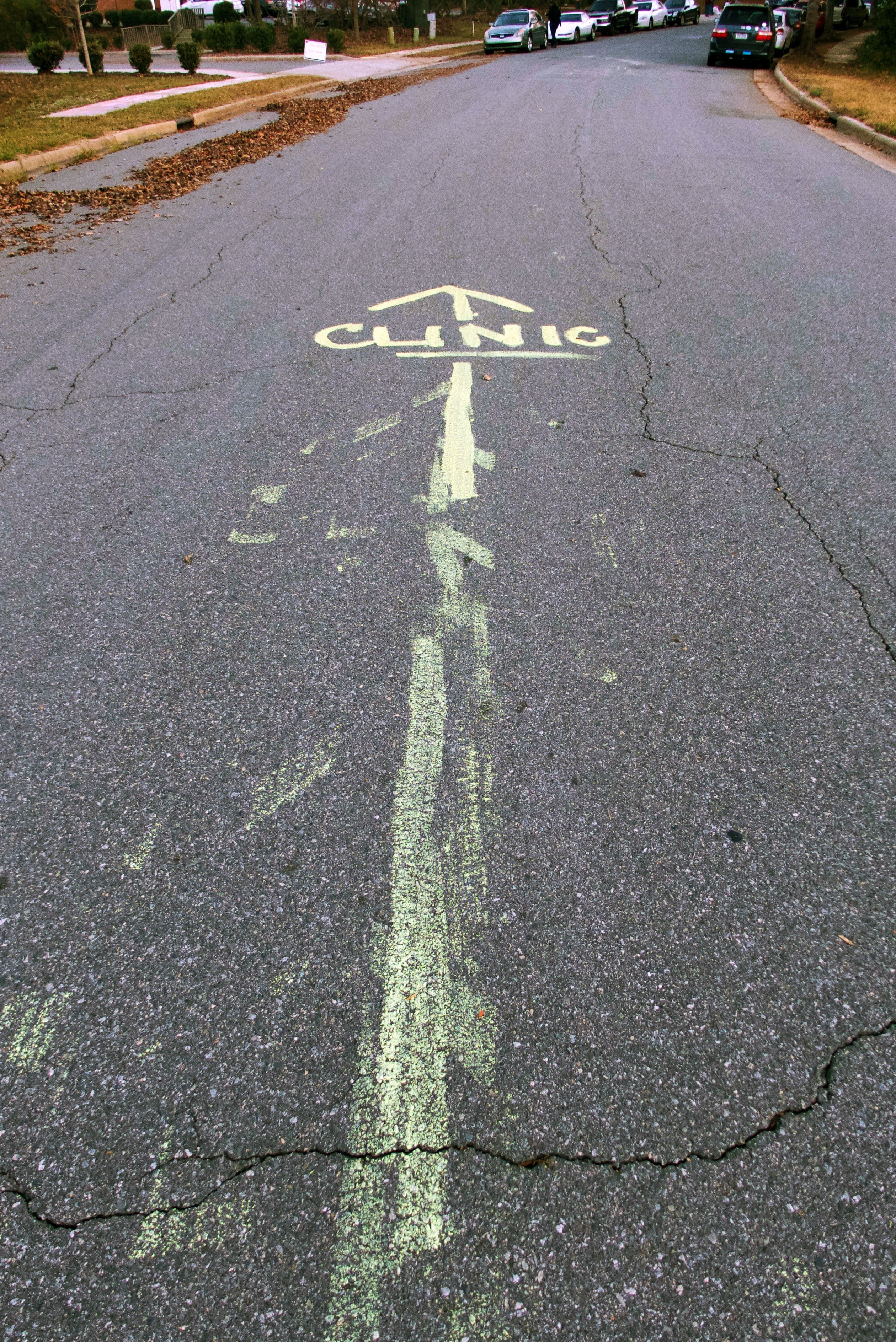 Directions to the clinic are painted on the street outside APWHC in Charlotte to avoid confusion with mobile crisis pregnancy