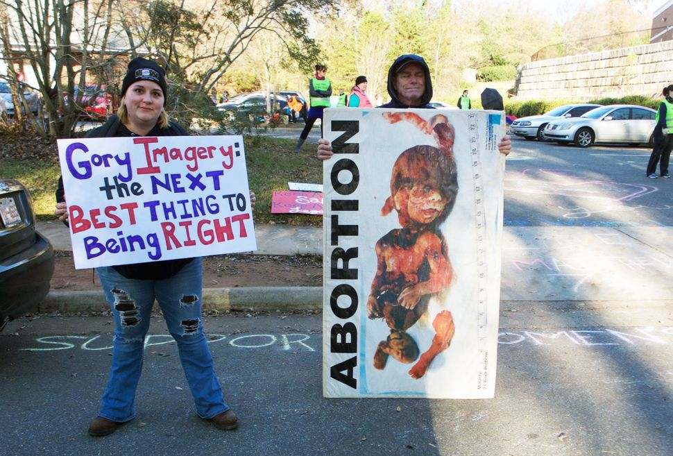 A pro-choice protester stands next to an anti-abortion protester at the entrance of APWHC Charlotte.