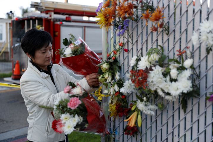 A woman places flowers at a makeshift memorial near the scene of a fire in the Fruitvale district of Oakland, California, Dec