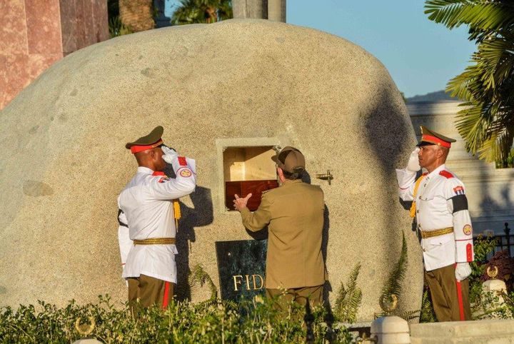Cuba's President Raul Castro (C) places the box containing the ashes of Cuba's former President Fidel Castro into a boulder a
