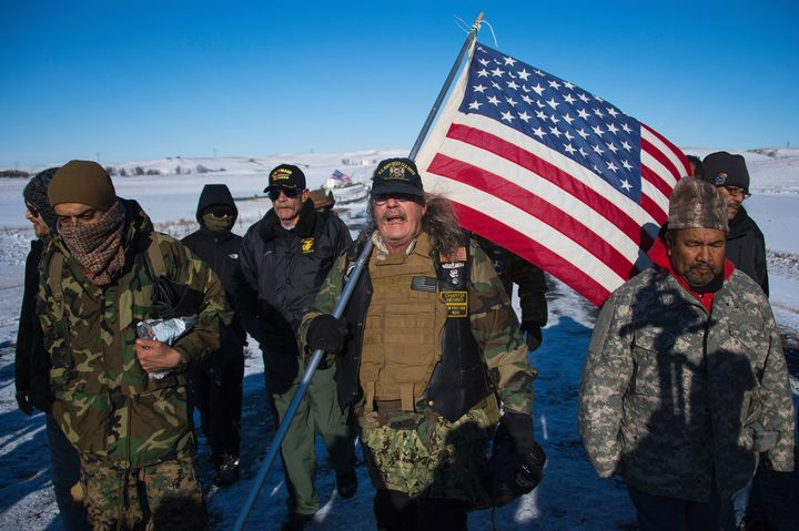 U.S. Navy deep sea diving veteran Rob McHaney (C) holds an American flag as he leads a group of veteran activists back from a police barricade on a bridge near Oceti Sakowin Camp on the edge of the Standing Rock Sioux Reservation.