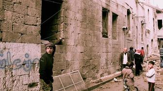 Residents survey the damage after a barrel bomb hit their street in oppositionheld areas of Aleppos Old City in January 2015