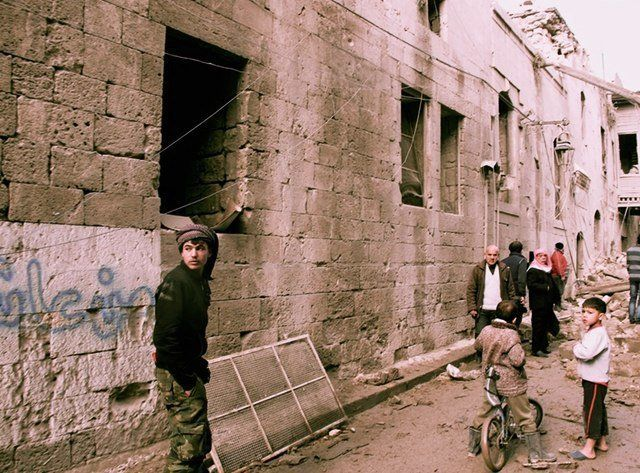 Residents survey the damage after a barrel bomb hit their street in opposition-held areas of Aleppo's Old City in January 201