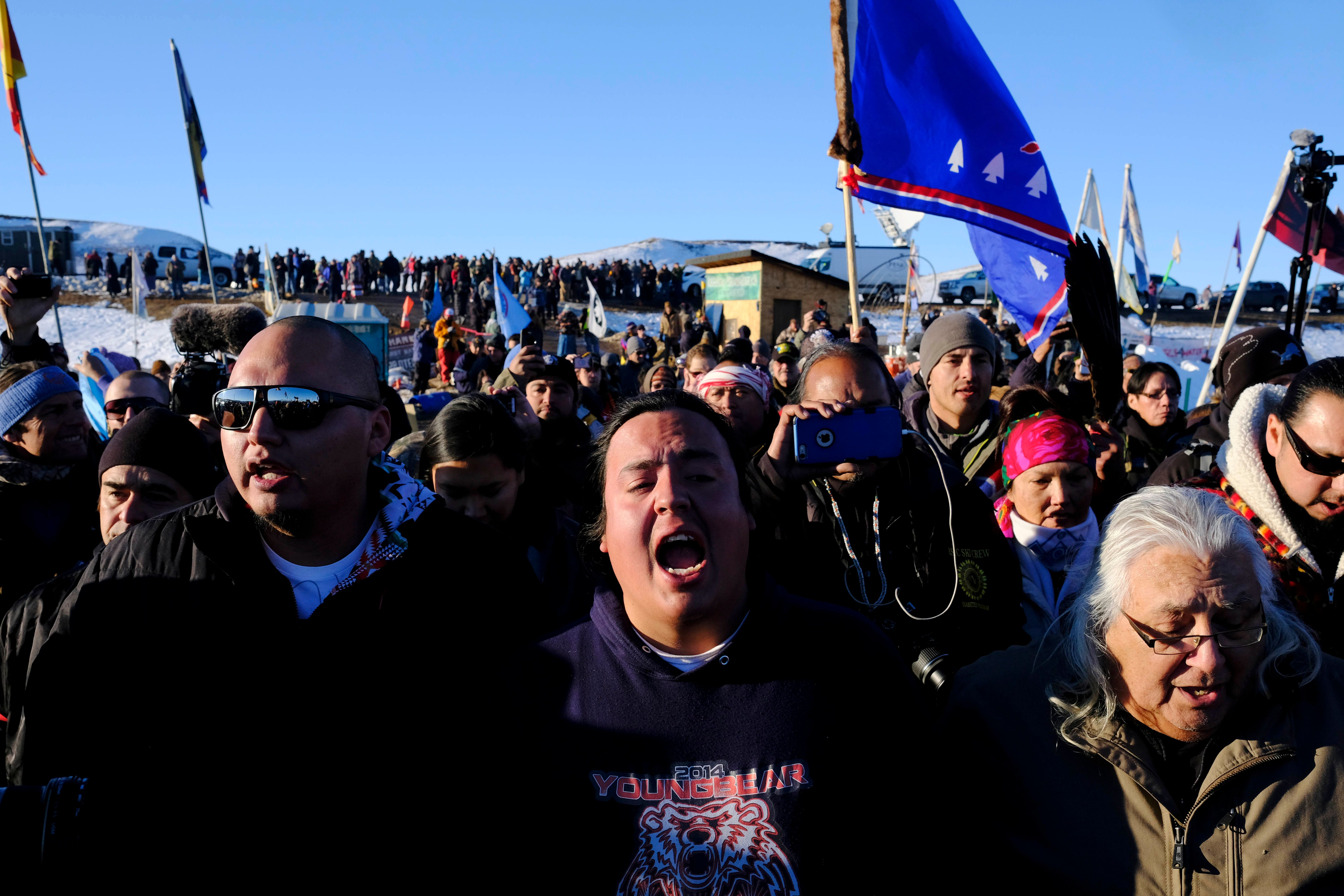 Dakota Access Pipeline protesters celebrate as they march back to the Oceti Sakowin campground after they found out the Army