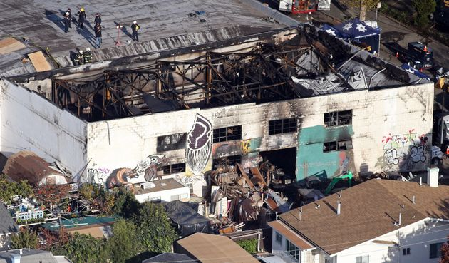 Recovery teams examine the charred remains of the two-story converted warehouse that caught fire, killing...