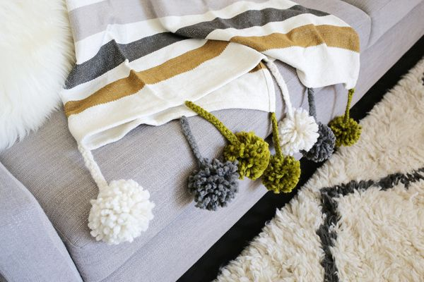 "<strong>Get the directions to create a <a href=""http://www.abeautifulmess.com/2015/10/pom-pom-blanket-diy.html"" target=""_blan"