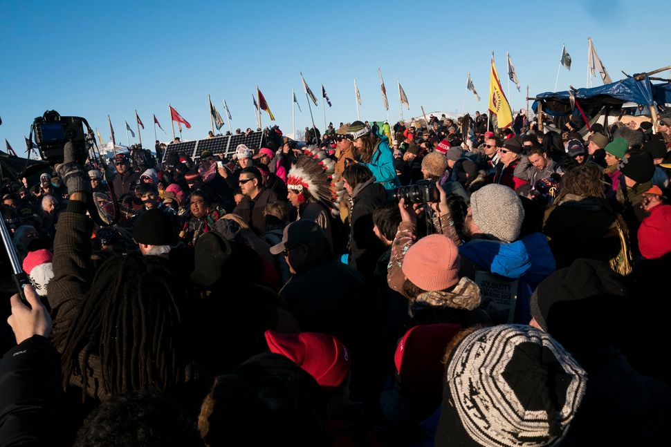 Thousands gather in the main area of the Oceti Sakowin campground to celebrate after the Army Corps of Engineers announced th