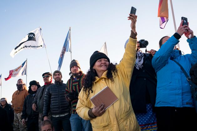 Dakota Access Pipeline protesters celebrate as they watch a group of veterans march into the Oceti Sakaowin