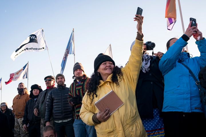 Dakota Access Pipeline protesters celebrate as they watch a group of veterans march into the Oceti Sakaowin camp.