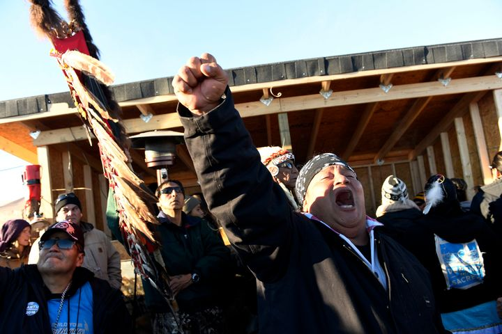 Troy Fairbanks, right, of the Standing Rock Sioux tribe cheers after hearing Chief Arvol Looking Horse announce to members of over 300 nations that the pipeline's construction has been halted.