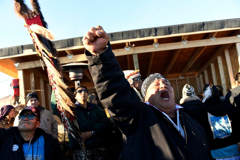 Troy Fairbanks, right, of the Standing Rock Sioux tribe cheers after hearing Chief Arvol Looking Horse announce to members of