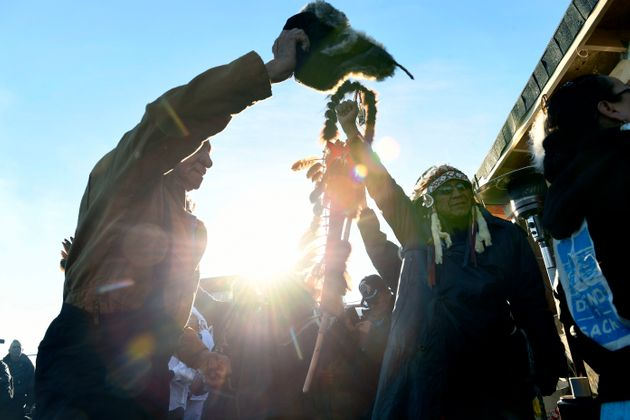 Native americans lift up their hands to celebrate their