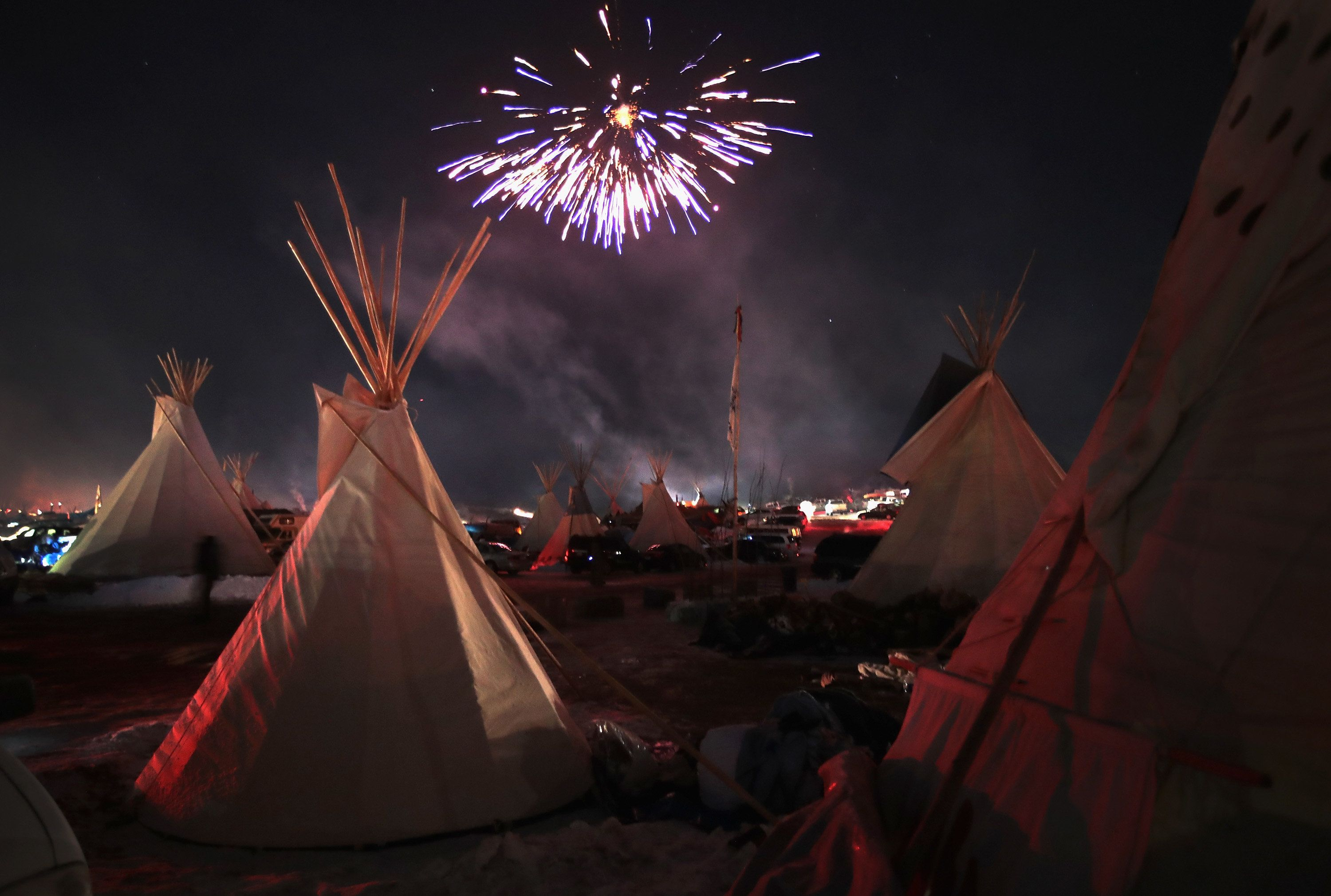 Fireworks fill the night sky above Oceti Sakowin Camp as activists celebrate after learning an easement had been denied for t