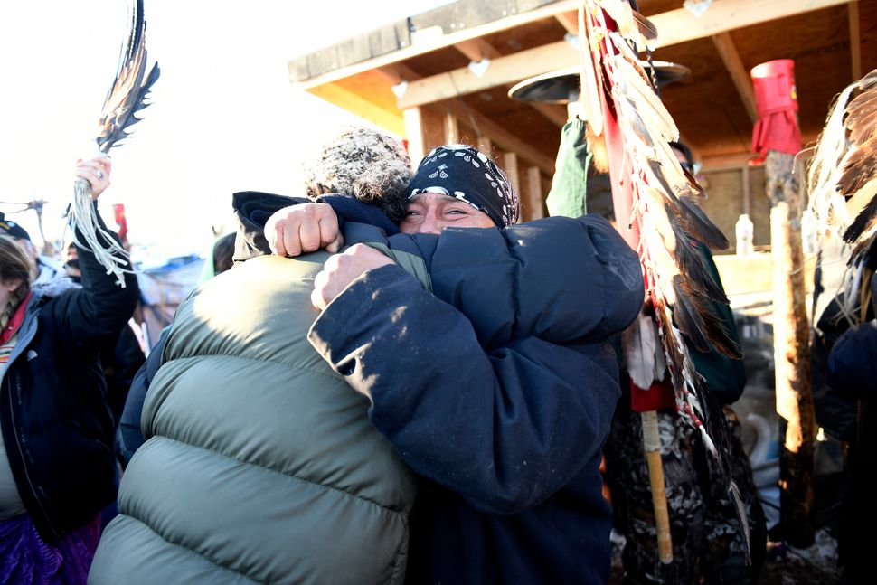 Troy Fairbanks, right, of the Standing Rock Sioux tribe, holds back tears as he hugs a friend after hearing Chief Arvol Looki