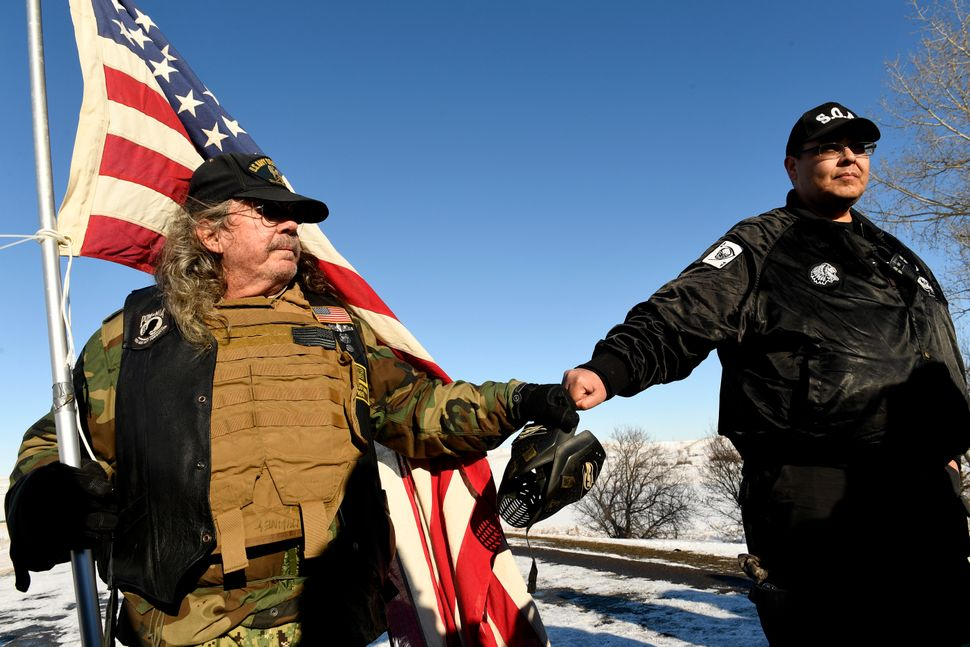 US Navy veteran Bob McHaney, left, and Bill Runningfisher, of the Gros Ventre nation, right, press their fists together in so